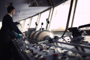 Navigation officer driving ship on the river.